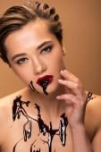 Fotografie schmutzige nackte Frau mit roten Lippen und Schokolade verschüttet auf der Haut berühren Gesicht isoliert auf beige