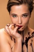 nackte Frau mit roten Lippen und Schokolade verschüttet auf der Haut leckt Finger isoliert auf beige