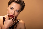 beautiful naked woman with red lips and chocolate spills on skin touching face isolated on beige