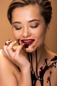Fotografie Lächeln nackte Frau mit roten Lippen und Schokolade verschüttet auf der Haut isoliert auf beige