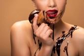 Fotografie Teilbild einer nackten Frau, die rote Lippen leckt, Schokolade auf der Haut verschüttet und Muffin isoliert auf beige hält