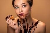 Fotografie schöne verträumte nackte Frau mit roten Lippen und Schokolade verschüttet auf der Haut essen Muffin isoliert auf beige