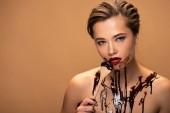 schöne nackte Frau mit roten Lippen und Schokolade verschüttet auf der Haut hält Holzlöffel isoliert auf beige