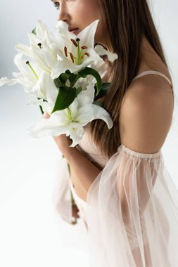 Cropped view of tender young woman holding lilies isolated on white stock vector