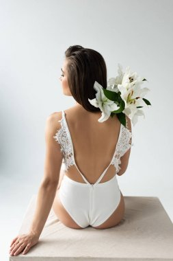 Back view of tender young woman in lacy bodysuit holding bouquet of lilies isolated on white stock vector