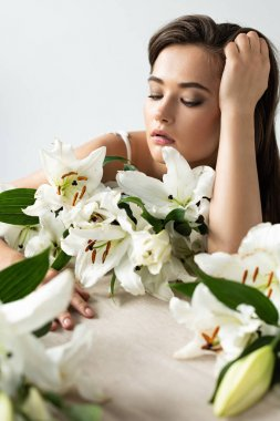 tender young woman near white lilies isolated on white