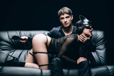 passionate man sitting with leather spanking paddle near sexy woman in bdsm costume on leather sofa isolated on black