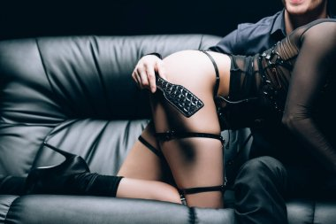 partial view of man holding bdsm spanking paddle near sexy woman on black leather sofa isolated on black