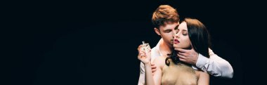 panoramic shot of young brunette woman holding perfume while boyfriend kissing her isolated on black