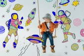 Photo cute kid in jeans and orange shirt sitting on swing and looking at fairy space with astronauts illustration on grey background