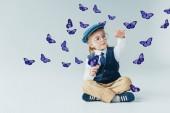 rozkošný chlapec, který sedí na podlaze s zkříženýma nohama mezi fialovými motýly na šedém pozadí