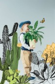 adorable kid in retro vest and cap holding plant in flowerpot on grey background with fairy cacti illustration
