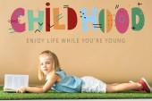 rozkošný kluk ležící na trávě a v knize na béžovém pozadí s dětským vyobrazením