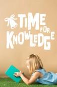 lächelndes und nettes Kind, das auf Grasteppich liegt und Buch auf beigem Hintergrund mit weißer Zeit für Wissensschrift hält