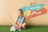 átgondolt aranyos gyermek ült keresztbe lábát fű szőnyeg és a gazdaság könyvet bézs háttérrel tudás hatalom betűkkel