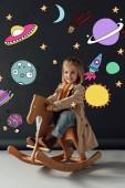šťastné dítě v zákopu a džínách, které sedí na houpacím koni na černém pozadí s pohádkovou kosmickou ilustrací