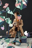 cute child in trench coat and jeans holding teddy bear on black background with fairy plants illustration