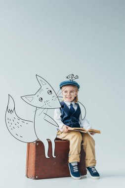 smiling kid in retro vest with fantasy bird on cap sitting on suitcase near fairy fox and holding book on grey background