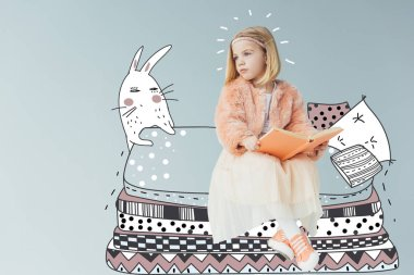 dreamy kid in faux fur coat and skirt sitting on fantasy bed with pillows near rabbit and holding book isolated on grey