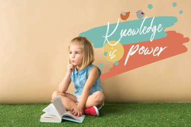 thoughtful cute child sitting with crossed legs on grass rug and holding book on beige background with knowledge is power lettering