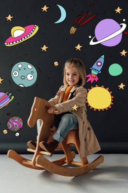 Happy child in trench coat and jeans sitting on rocking horse on black background with fairy cosmic illustration stock vector