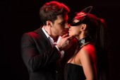 man in formal wear kissing bdsm girl isolated on black