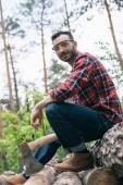 mosolygós lumberer nézi kamera ülve bejelentkezik az erdőben és a gazdaság AX