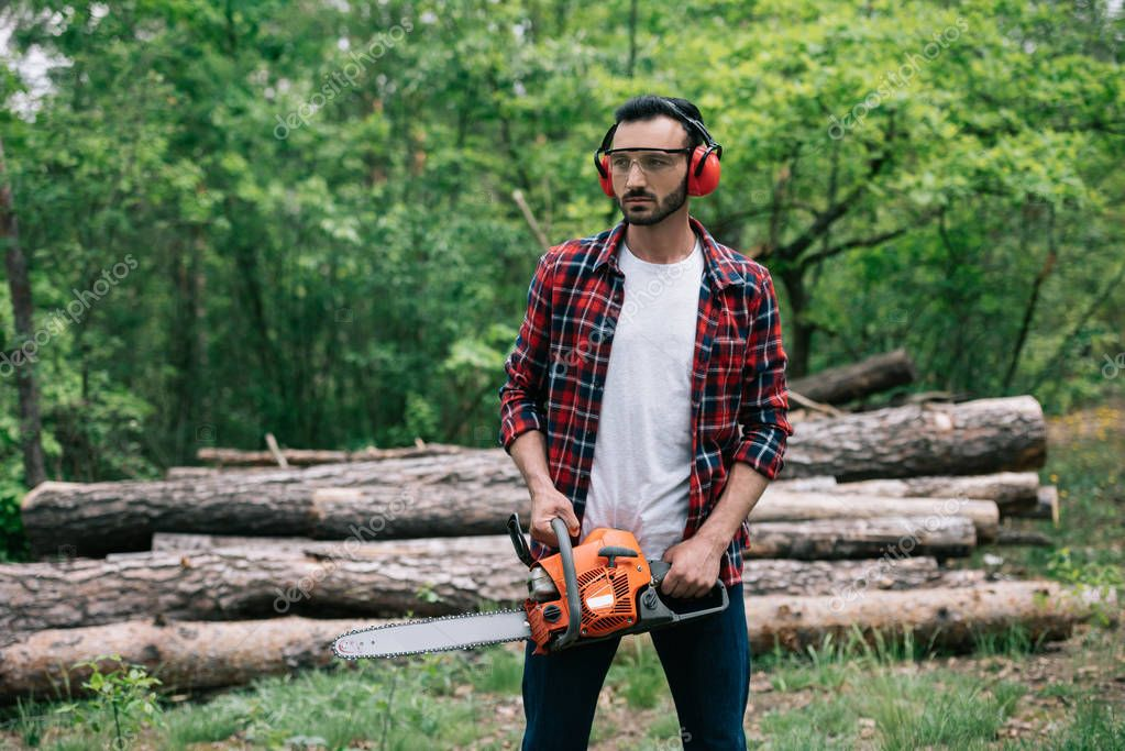 handsome bearded lumberer in protective glasses and noise-canceling headphones holding chainsaw in forest