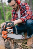 selective focus of lumberjack repairing electric chainsaw in forest