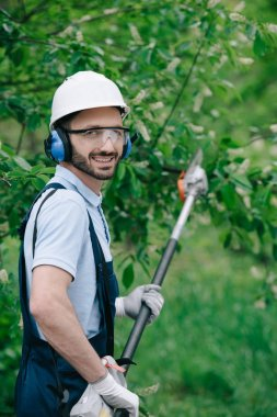 cheerful gardener in helmet, protective glasses and noise-canceling headphones holding telescopic pole saw and smiling at camera