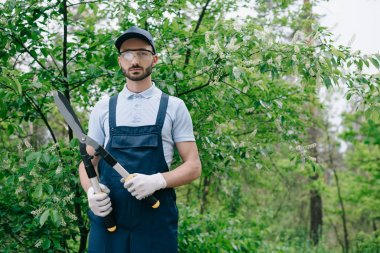 serious gardener in overalls, cap and protective glasses holding trimmer and smiling at camera