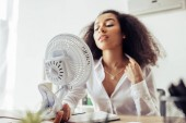 selective focus of attractive african american businesswoman holding electric fan while sitting at workplace