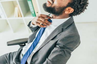 partial view of african american businessman touching tie while suffering from heat in office