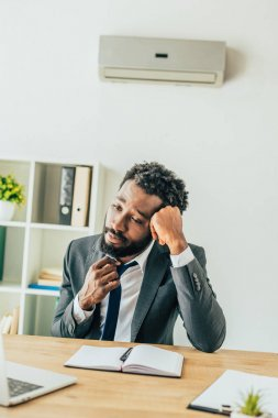 exhausted african american businessman sitting at workplace under air conditioner and suffering from heat