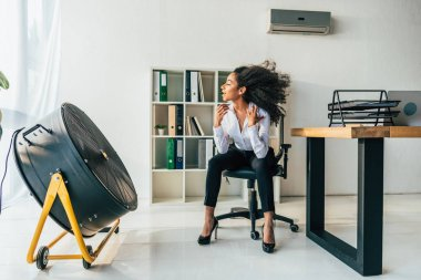 pretty african american businesswoman sitting on office chair in front of blowing electric fan