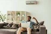 csinos afrikai ember használ laptop rövid idő ülő-ra dívány alatt klíma és tárolás távoli ellenőr