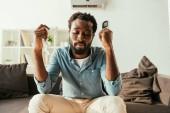 kimerült afrikai ember gazdaságban szalvétára és a távoli vezérlő ülve a kanapén, és szenved hőtől
