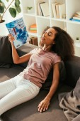 exhausted african american woman waving with magazine while sitting on sofa with closed eyes and suffering from summer heat