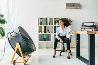 smiling african american businesswoman sitting on office chair in front of electric ventilator in office