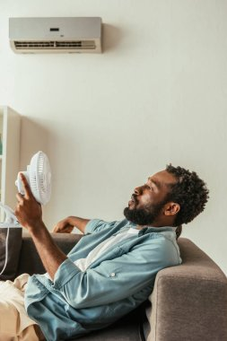 african american man holding blowing electric fan while lying on sofa under air conditioner