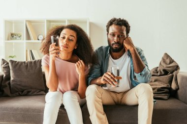 exhausted african american man and woman drinking water from glasses while sitting on couch and suffering from summer heat at home