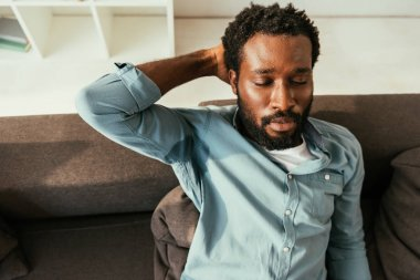 exhausted african american man in sweaty shirt sitting on couch and suffering from heat with closed eyes