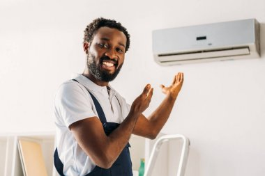 cheerful african american repairman smiling at camera and pointing with hands at air conditioner