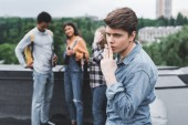 selective focus of teen smoking cigarette and looking away