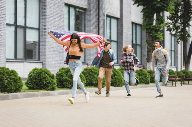 happy teenagers smiling, holding american flag and running outside