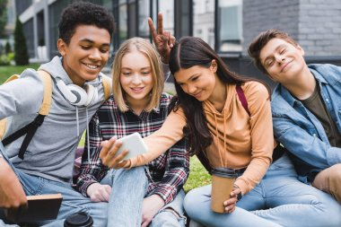 smiling and happy teenagers sitting on grass and taking selfie