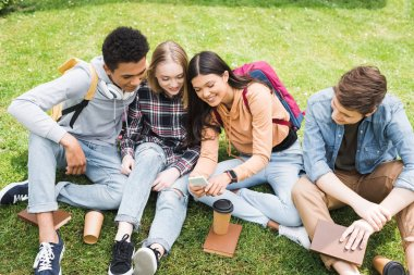 smiling and happy teenagers sitting on grass and looking at smartphone