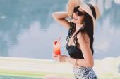 felice bella bella donna bruna giovane in costume da bagno, cappello di paglia e occhiali da sole sorridente mentre in possesso di cocktail vicino allacqua