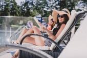 célzott összpontosítás két boldog nők napozás és olvasás folyóiratok