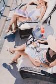 a medence közelében ülő nők és az olvasófolyóiratok általános nézete